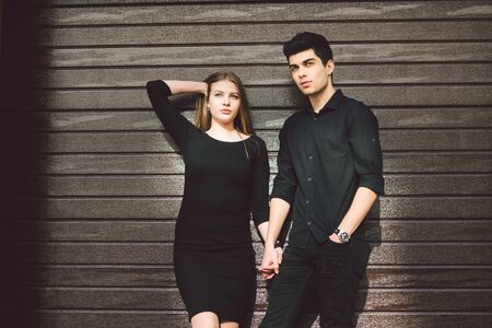 Multiracial stylish couple in black clothes posing on a background of a wooden wall. Turkish guy and caucasian girl date and love. Muslim man and gurney woman together.