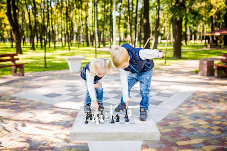 Hobby of Children, Boy and Girl Playing Chess. Funny little brother and sister playing outdoor chess in the park on a public site. Hobby club children playing Logic gameg chess with figures.
