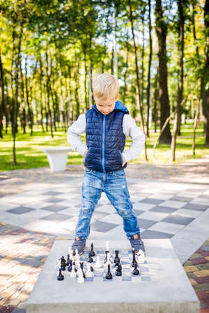 A funny boy of Caucasian ethnicity is playing on a public chess venue in a city park. Children frolic and indulge instead of studying. The topic of hyperactivity in children. 写真素材