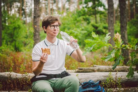 Female hiker eating sandwich in nature. Woman tourist having breakfast or lunch at picnic, eating hot sandwiches while spending time in nature. traveler stopped rest and eat campfire toasted sandwich.