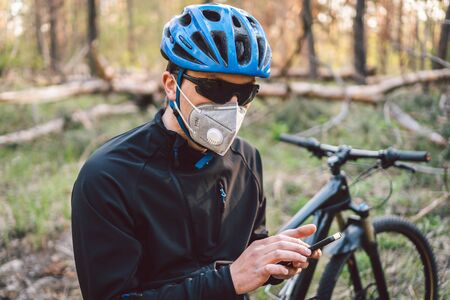 Male cyclist wearing face respirator, with filter pm 2.5. theme Coronavirus Or Covid 19. Athlete in protective mask with bicycle, air pollution concept. A man with bicycle in forest uses mobile phone.