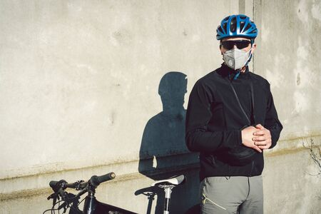 Portrait male cyclist near gray concrete wall in protective respirator PM 2.5 with filter. Protect human respiratory organs from dust and suspended particles in air, infection with infectious diseases