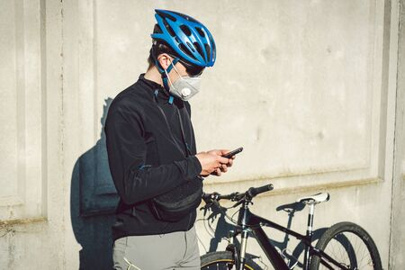 Man using smart phone while standing by bicycle against gray wall. Chilling after good ride. courier in protective mask on bicycle stopped and watching phone application. Delivery service quarantine.