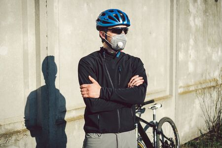 Cyclist in face mask due to smog in the city. Bike courier making a delivery. Man wearing covid 19 coronavirus mask. Cyclist in pollution mask from bushfire smoke haze. Delivery Service.