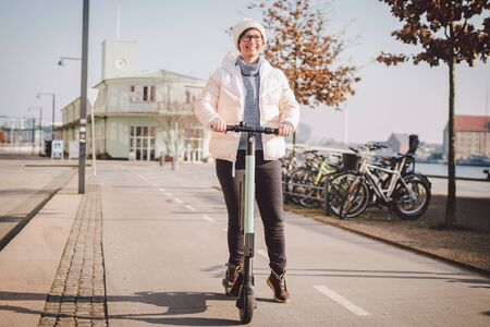 Tourist woman rent Electric scooter in danish capital Copenhagen. Female holding steering column knob with electric kick scooter handle on street in europe on sunny winter day.