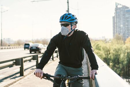 Male cyclist wearing respirator face mask with heavy duty protective filter. Man on bike wearing respirator face mask with heavy duty protective filter. Safety breathing masks. Pollution concept.