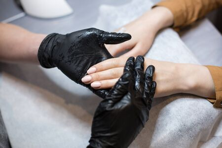 Close-up of a manicurist doing moisturizing and hand massage for a client. The theme is skin care and body beauty. Spa and Manicure concept. Soft skin. Cosmetology, applying.