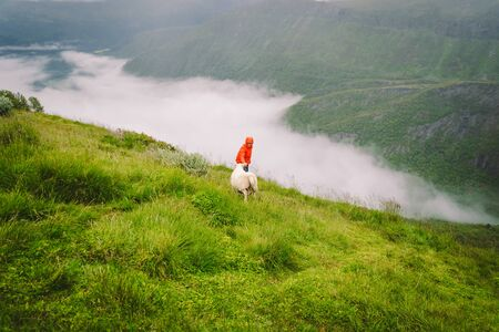 Woman hiker posing on mountain in norway, rainy weather near sheep. Tourist and cattle on clearing in hill area, north norge in foggy. exploring nature in Scandinavia.