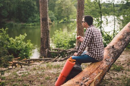 The theme is healthy eating and vegetarianism. Outdoor activities in the forest and fruit snack. Young Caucasian male hiker resting and eating an apple in a clearing near a forest lake. Banco de Imagens