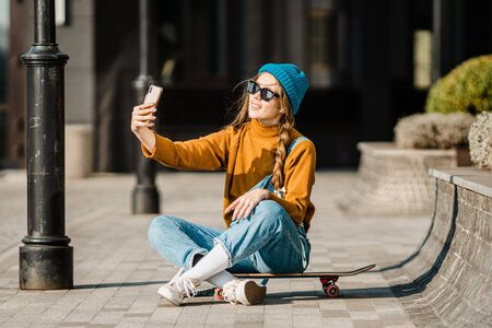Cute urban girl outdoors with skateboard using smart phone. Happy young woman with skateboard, headphones and cell phone. Hipster female sit on skate board and using mobile phone.