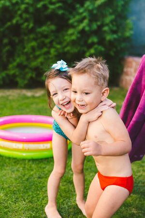 Happy Caucasian children play, wrapped in a large summer beach towel in the heat after swimming in a round home inflatable pool. kids warm up in towels after swimming. during summer vacation. Stockfoto - 148860219