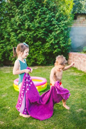 Happy Caucasian children play, wrapped in a large summer beach towel in the heat after swimming in a round home inflatable pool. kids warm up in towels after swimming. during summer vacation.