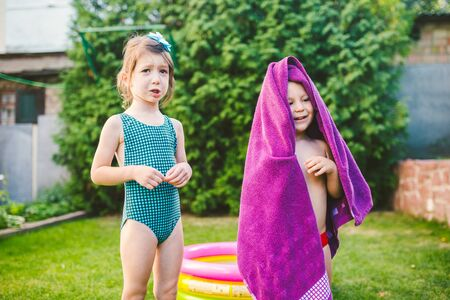 Happy Caucasian children play, wrapped in a large summer beach towel in the heat after swimming in a round home inflatable pool. kids warm up in towels after swimming. during summer vacation. Stockfoto - 148860281