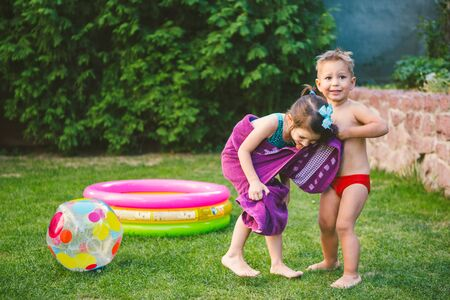 Children wrapped in a beach towel during summer vacation. Wet kids on summer swimming pool with towel. babies having happy time on summer basin. Theme of summer heat and vacation at home.
