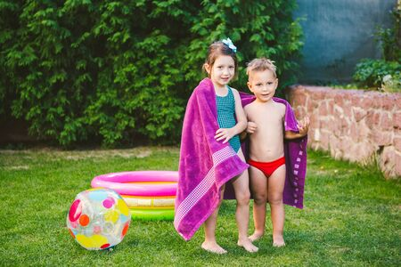 Happy Caucasian children play, wrapped in a large summer beach towel in the heat after swimming in a round home inflatable pool. kids warm up in towels after swimming. during summer vacation. Stockfoto - 148860288
