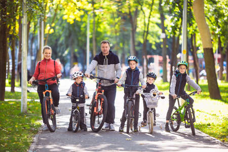 Theme family active sports outdoor recreation. A group of people is a big family of 6 people standing posing on mountain bikes in a city park on a road on a sunny day in autumn.