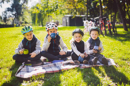 Theme active family holidays nature. group people small little children three brothers and sister sit onblanket near bicycles in park green grass lawn rest and drink drink from cups