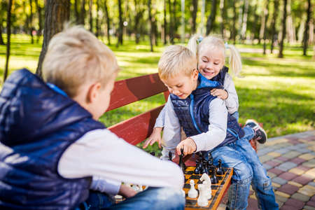 Caucasian children play chess on wooden chessboard in park bench. Brothers and sister big friendly active mental family spend time on vacation in sunny weather. Children's chess club. Chess sport. Banco de Imagens