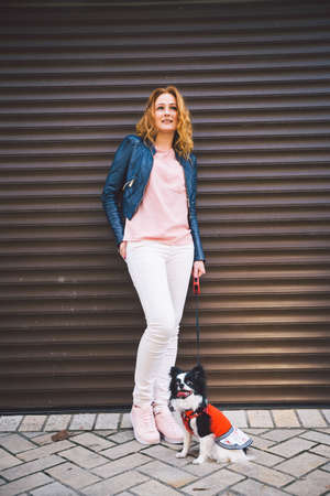 A young Caucasian red-haired woman stands near a city embossed wall with her pet dog, a Chihuahua breed. Walk with a funny dog in clothes. Chihuahua in a dress. Urban and lifestyle concept. 스톡 콘텐츠