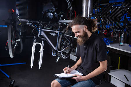 Bicycle Workshop Technician Doing Administrative Work. Bicycle mechanic writing in his checklist notebook. Bicycle mechanic at work. Caucasian worker writing on clipboard in bicycle shop.