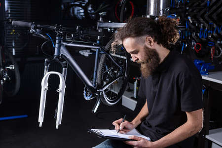 Stylish bicycle mechanic making notes in clipboard in workshop. theme small business selling, repair and service bicycles. Technician Doing Administrative paperwork in bike shop. Manage business.