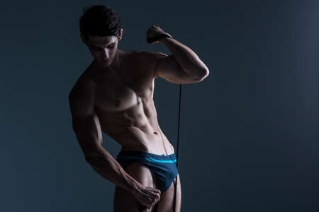 Muscular fitness young male antique perfect muscles six packs of abs and bare chest. Bodybuilder model trains with a stretching elastic against a dark background in the studio. Workout training gym.