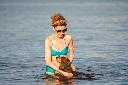 Mature caucasian woman plays ball in water with dog of Dachshund breed. Summertime theme with pet swim in river. Hot weather in summer. Chilling in ake. Owner and dog. Active leisure on beach.