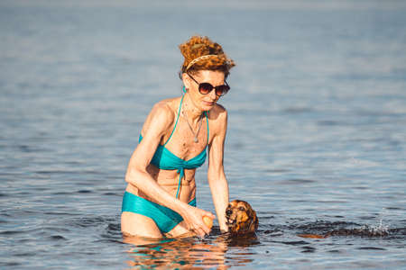 elderly woman enjoying outdoor activities playing ball in river swimming with her cute dog Dachshund breed. concept pets, love for animals. woman in a swimsuit threw ball for canine companion.
