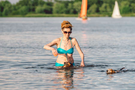 Caucasian elderly woman having fun on summer weekend with her dog breed dachshund in the water. Senior woman enjoying outdoor activities in the river swimming with her cute dog. Pets concept.
