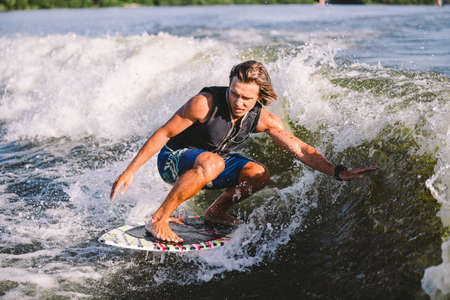 Young athletic man with long hair wakesurfing on waves of river in sunny summer weather. Ttheme outdoor activities in summer. Water sports wakesurf on the board. sliding wakeboarder in water splash. 免版税图像