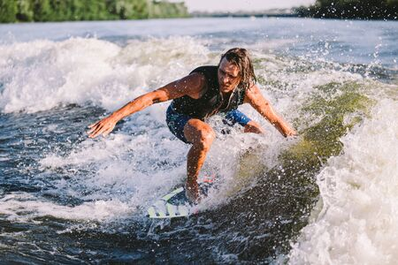 A man is surfing on a surfboard drawn by a motor boat above the wave of the boat. Weixerfer is engaged in surfing, entertainment, leisure, water sports. Athlete glides on the waves on the board. Stock Photo
