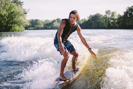 Beautiful long haired blond wakesurf in vest on board along waves of lake. Athletic male athlete wakes surfing in summer on river. Wakesurf water sport. Surfer on wave. Man surfing on the Surfboard. 免版税图像