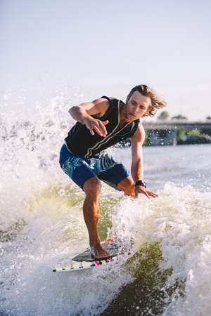 A man is surfing on a surfboard drawn by a motor boat above the wave of the boat. Weixerfer is engaged in surfing, entertainment, leisure, water sports. Athlete glides on the waves on the board. 免版税图像