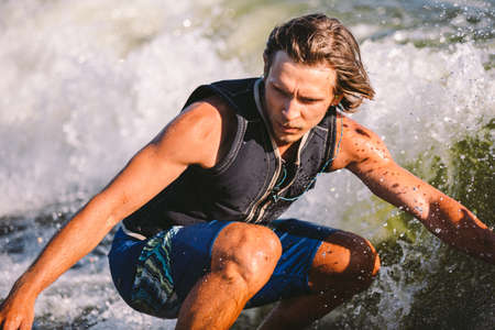 Active wakesurfer jumping on wake board down the river waves. Surfer on wave. Male athlete training on wakesurf training. Active water sports in open air on board. A man catches a wave on surf.