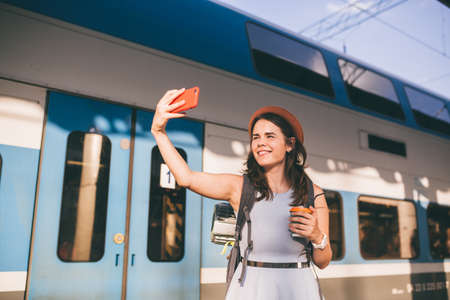 Cheerful woman traveler with backpack taking photo. selfie in train station. Travel lifestyle concept. woman shoot photo of yourself, using smartphone on railway station. backpacker use smart phone.