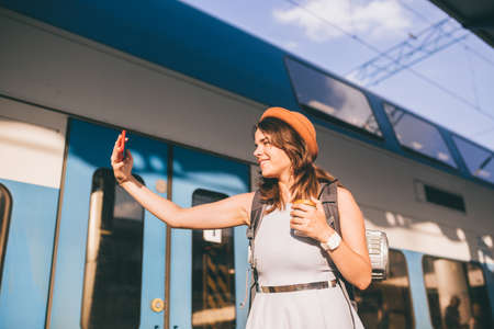 Theme travel, travel by rail. Beautiful caucasian woman in dress and backpack uses phone near railway carriage at station. A tourist takes selfie at train station. photo of yourself on railway track.