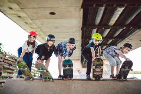 Extreme sport in city. Skateboarding Club for children. Group friends posing on ramp at skatepark. Early adolescence in skate training. Friends skateboarders on street platform for skating on board.