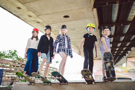 Group of friends children at skate ramp. Portrait of confident early teenage friends hanging out at outdoor city skate park. Little skateboarders posing with boards from above on ramp in skate park.