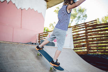 Skater boy rides on skateboard at skate park ramp. Kid practising skateboarding outdoors on skatepark. Youth culture of leisure and sports. Skateboarder doing trick on skateboard on halfpipe ramp.