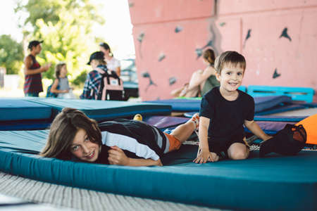Happy children playing lying on trampoline. Brothers are having fun lying on a sports mat on a trampoline in the gym outside. Boys indulge, laugh and hug each other after training. Stock fotó