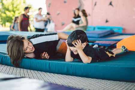 Happy children playing lying on trampoline. Brothers are having fun lying on a sports mat on a trampoline in the gym outside. Boys indulge, laugh and hug each other after training. Stock Photo