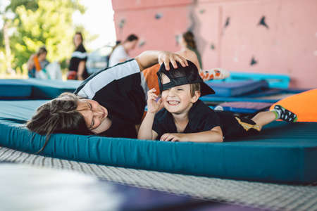Two brothers have fun lying on trampoline mat in outdoor sports center. Cheerful boys are fighting, hugging on trampoline after training. The theme of active relaxation, childhood and porty lifestyle.