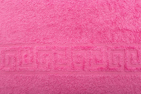 Terry towel, texture, textile background close up. Terry pink towel background. Color pink terry towel made of cotton fabric. Structure with uncut thread loops. pink towel background.