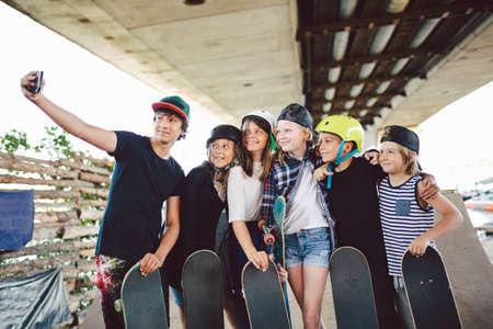 large group friends children skateboarders make videos, online broadcasts, video calls on phone in skate park. Kids spend time on skateboarding training, take selfie photo, embracing together.
