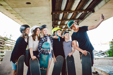 group of skateboarders children make social media content on phone while spending time on ramp in skate park. Friends stand together with skate boards hugging and taking selfie photo on smartphone.