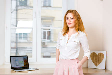 Successful Scandinavian entrepreneur, business woman promoted to employee. Confident worker with arms crossed standing in modern office on window background, proud of achievements, business going up. 免版税图像