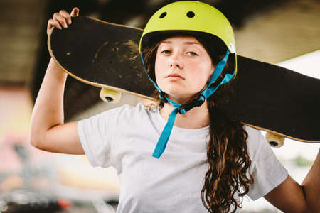 Close up of young attractive girl with skateboard standing outdoors in skate park. Female skateboarder holding her skate behind. Urban skateboarder girl skateboarding at skatepark ramp.
