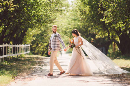 Lovely wedding couple wood forest. Bride and groom, follow me, married couple, woman in white wedding dress and veil. Rustic outdoors love story. Follow me hipster photo. newlyweds holding hand walk. Banque d'images