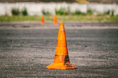 Close-up of an old dirty orange traffic cone at the site for driving training or auto school. Plastic red markings at the autodrome, extreme driving stadium. Driving school concept.