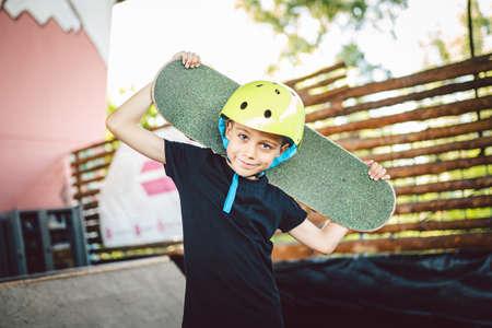 Portrait boy holding skateboard over shoulder. Beautiful kid model posing on skate board park. Portrait stylish child with skate board on half pipe ramp an outdoor skate park. Sport, children health.